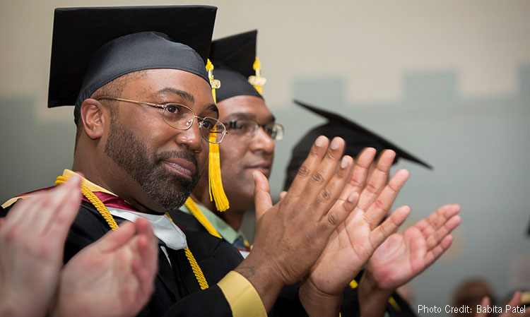 Sullivan Correctional Facility graduate wearing cap and gown, smiling and clapping