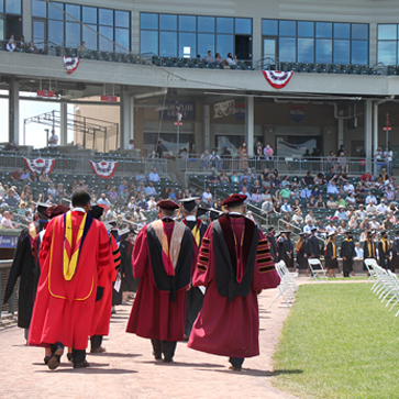 Members of the Stage Party-President Daly, Dr. Ozuah, Peter Skae, and others walk on the field towards graduates at Ceremony
