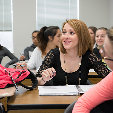 STAC Education student sitting in classroom holding pen at her desk, candid photo, smiling.