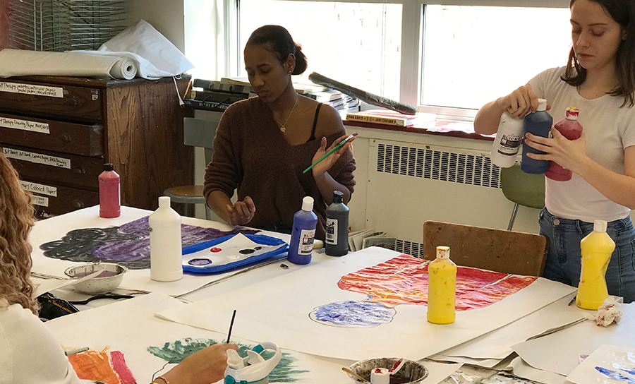 Art therapy classroom setting with students painting at a table