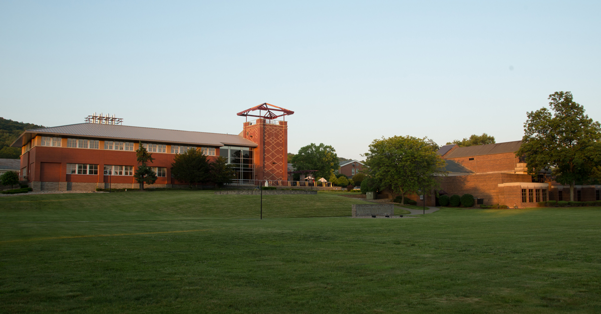 Costello Hall tower and brick building in background; Romano front lawn in foreground, green grass blue sky