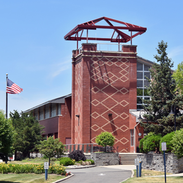 Costello Hall tower outside blue sky background American flag to left