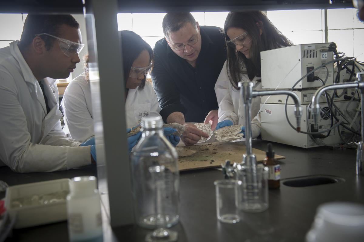 Science Professor working with students in a lab