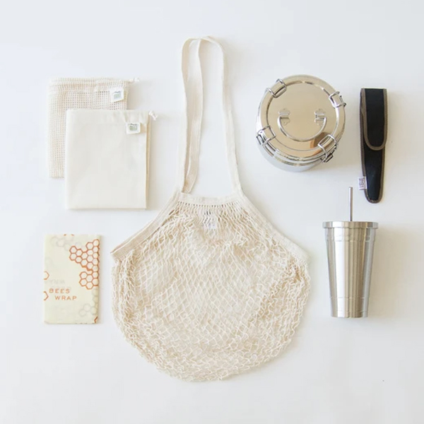 zero waste kit of a mesh bag, bee's wrap for food, cloth bags, metal container and metal cup with straw