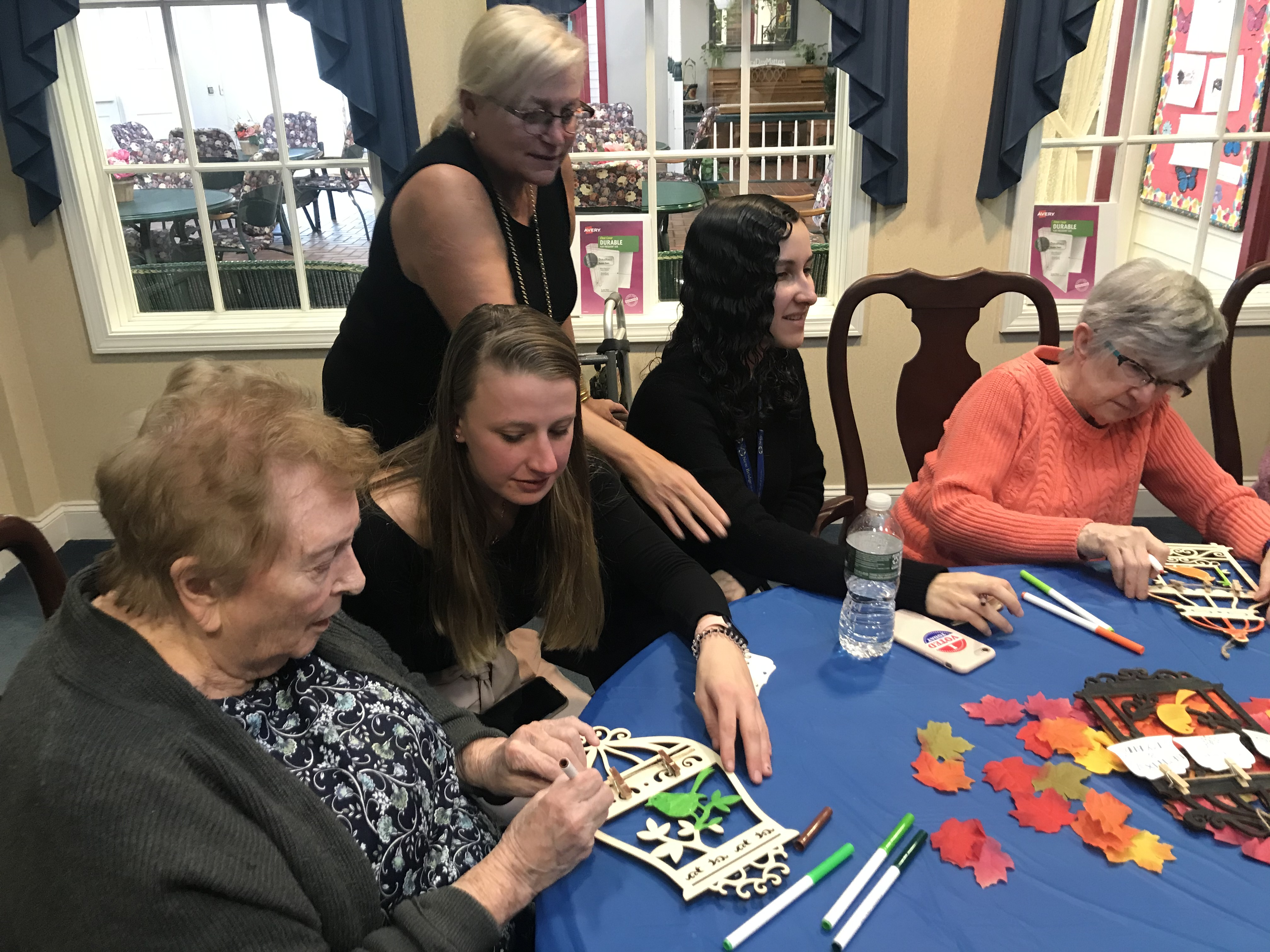 Two STAC Therapeutic Recreation students sitting with participants in a senior center working on arts and crafts fall season project. Leaves; coloring bird house wall decor with markers; Dr. Levine-Madori standing and observing