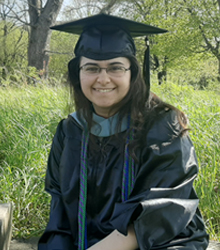 Jessica Vento smiling, wearing cap and gown after undergraduate commencement