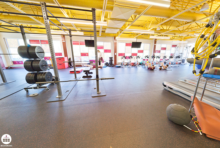 Portion of Kraus Fitness Center with students doing stomach crunches and spin bikes in the background