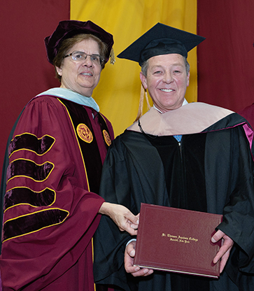 Margaret Fitzpatrick and Billy Procida on stage smiling, Margaret awarding Billy with honorary degree