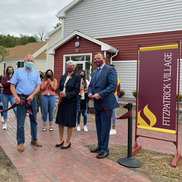 Dr. Margaret Fitzpatrick, President Ken Daly, and Werner Construction cutting ribbon outside of new dorm