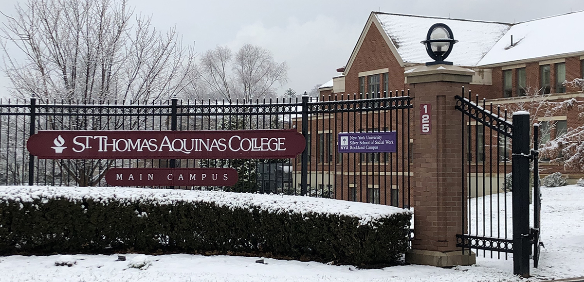 STAC entrance gate with STAC maroon and white logo; snow on ground. Borelli Hall in background
