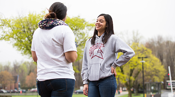 Two STAC students chatting outside wearing STAC sweatshirt