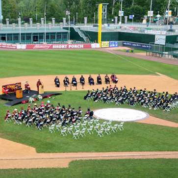 STAC students on field at commencement ceremony for class of 2020. Stage on left faculty and board members near stage