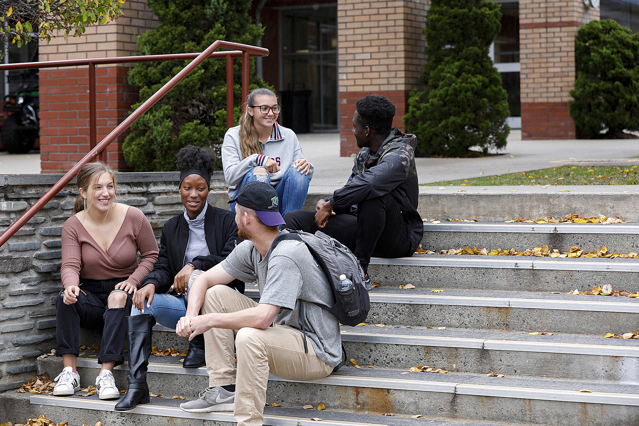 five stac students sitting on steps outside of Costello hall chatting and smiling