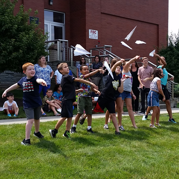 Seven elementary school children outside on grass near Costello Hall throwing their paper airplanes