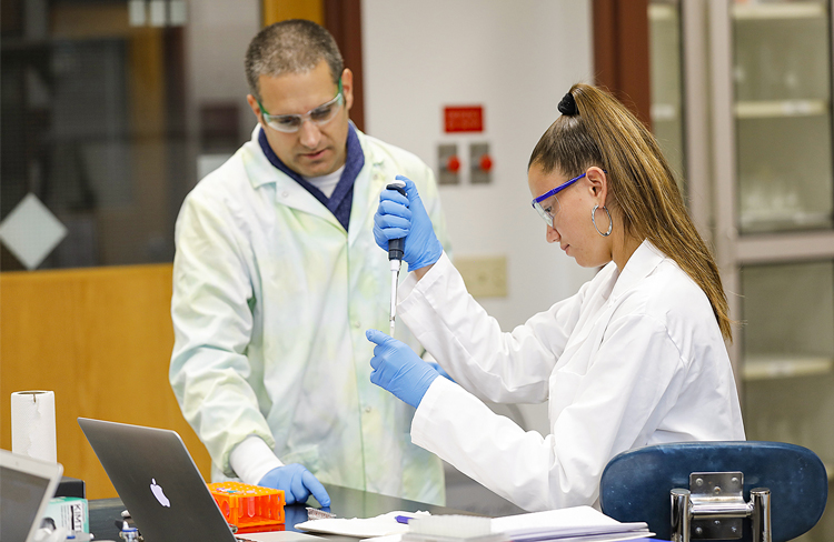 Dr. Ryan Wynne and student in lab using pipette; wearing lab coats, gloves, and glasses