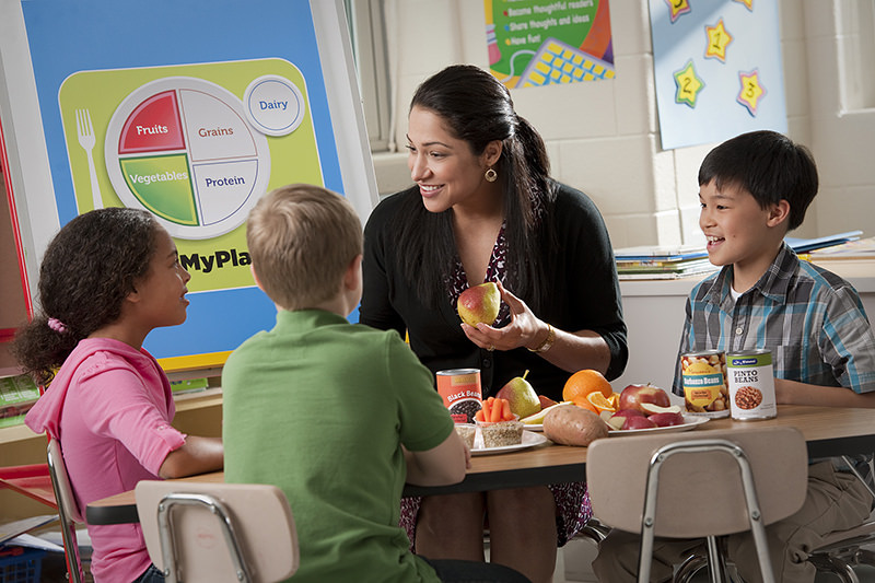 Woman teaching three kids in classroom