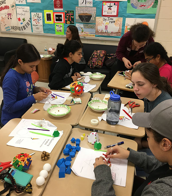 stac students working with high school girls on math projects