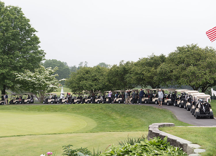 golf carts lined up at the start of the golf tournament