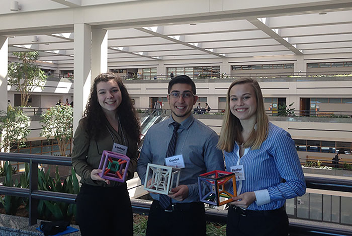 Lindsey, Daniel and Heather pictured with their dimensional cubes.