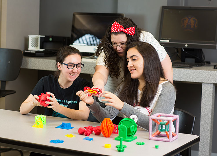 Two female students working with a female professor in the lab with 3D printers