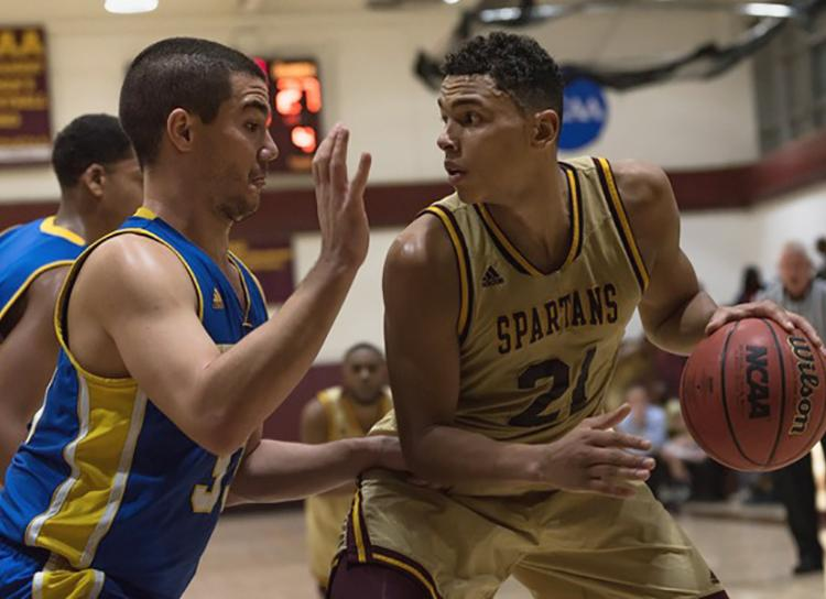 Image of STAC's Justin Reyes '18, with a basketball during a basketball game