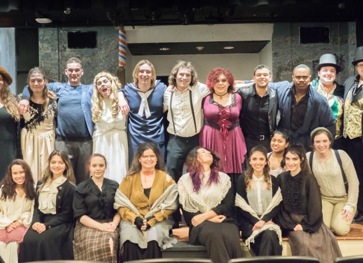 Entire cast of 20 STAC students on stage posing as a group in era-based attire, dresses, suits for cast photo of Sweeney Todd