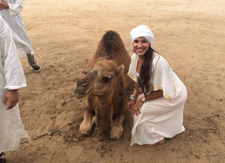 woman next to a camel