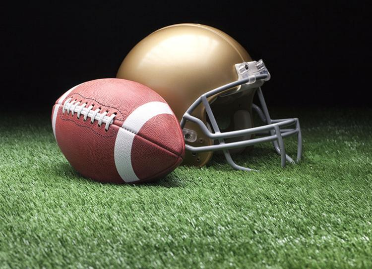image of football field with football and gold helmet