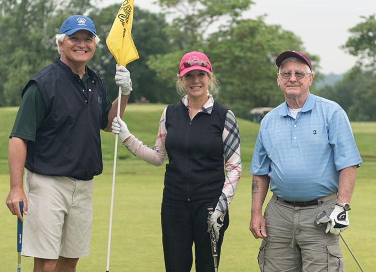 one female and two male golfers pose for a picture in between holes