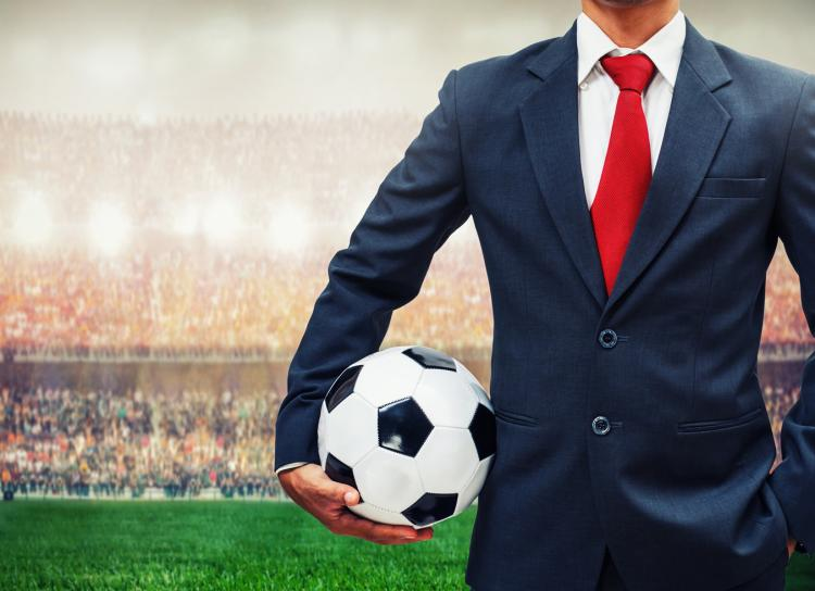 Image of a man wearing a tuxedo holding a soccer ball