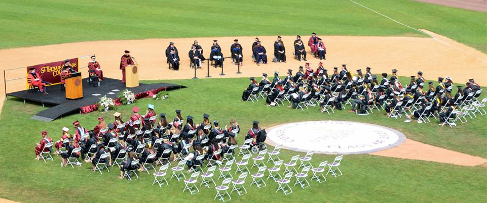 Commencement 2020 aerial view of students at chairs on baseball field, stage in front