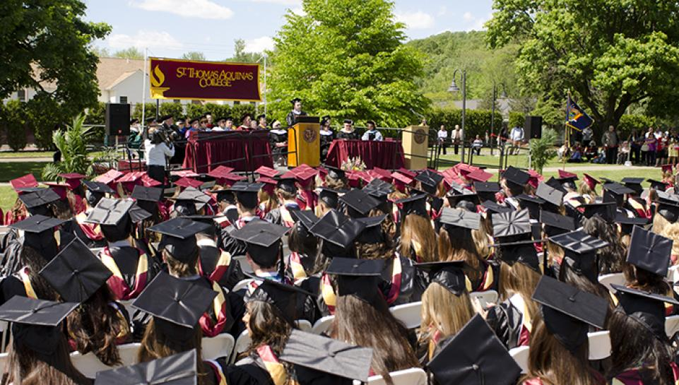 outdoor commencement ceremony showing graduates