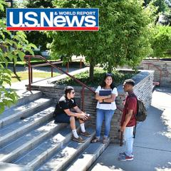 3 STAC students outside on Costello Hall Poggi Pavillion steps talking. Tree in background; U.S. News red white and blue logo