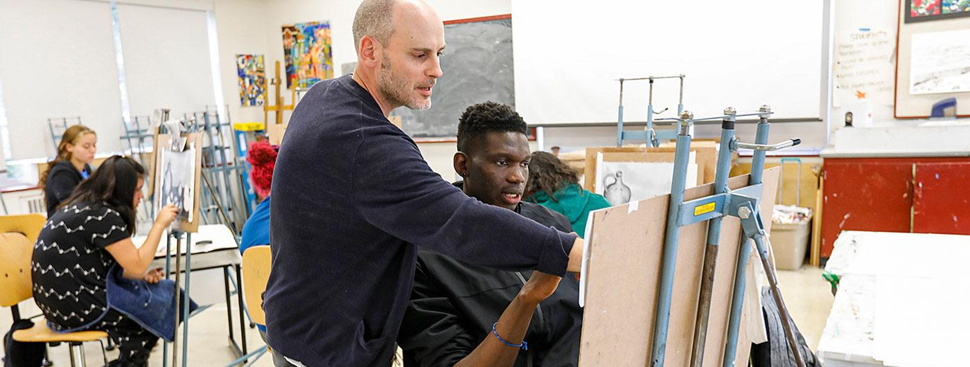 Student, George Nkrumah Meziah & art Professor Timothy Hull, in art classroom discussing George's canvas piece. Sitting on stool