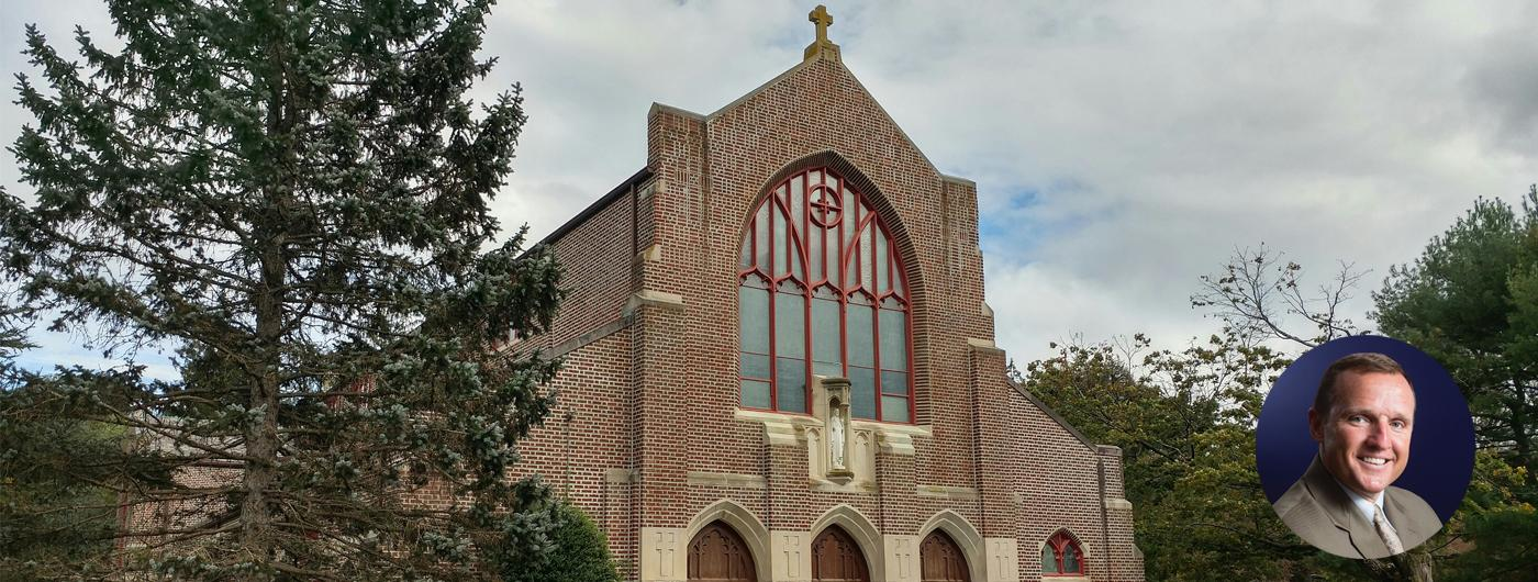 Sacred Heart Chapel brick building with cross on roof and trees surrounding chapel building