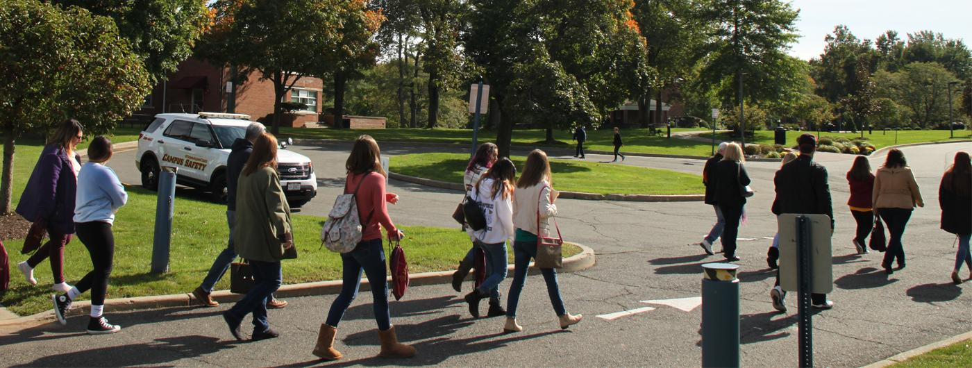 group of students and families walking near Borelli Hall and Maguire circle outside on a tour of campus, sunshine, green trees