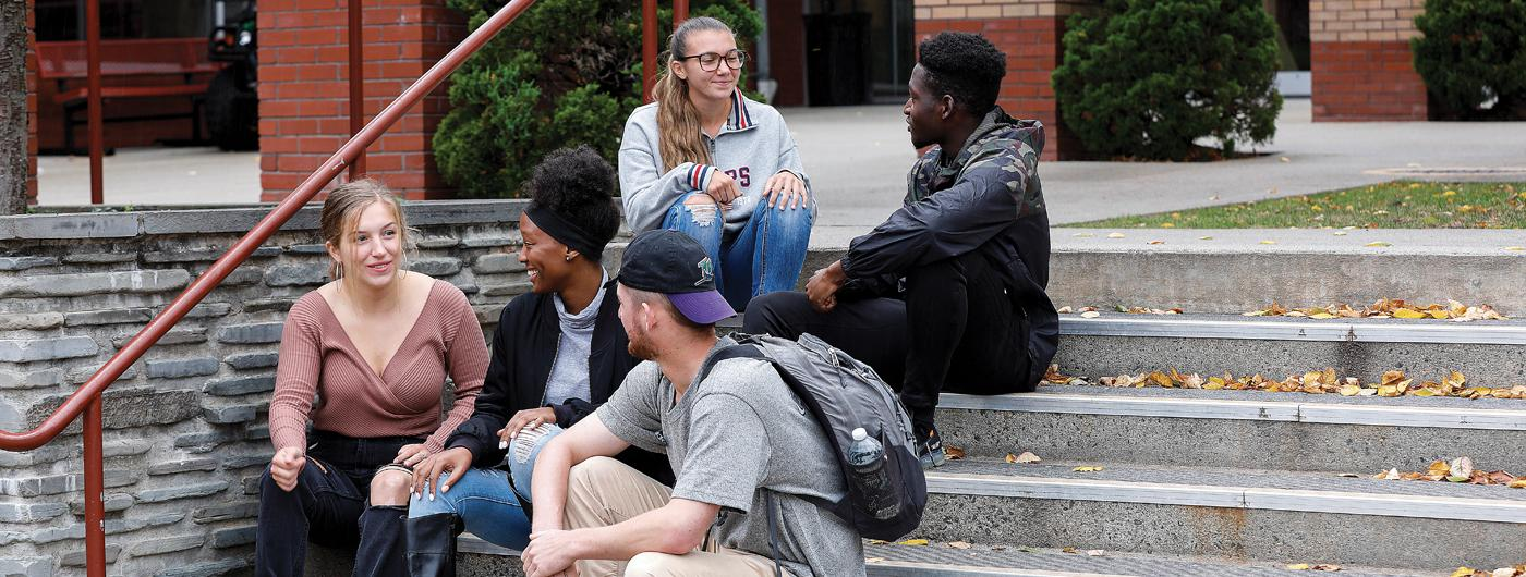 5 Students sitting on STAC campus steps and chatting