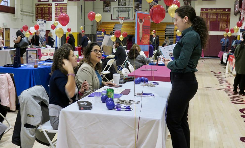 student interacts with potential employer at the job and internship fair