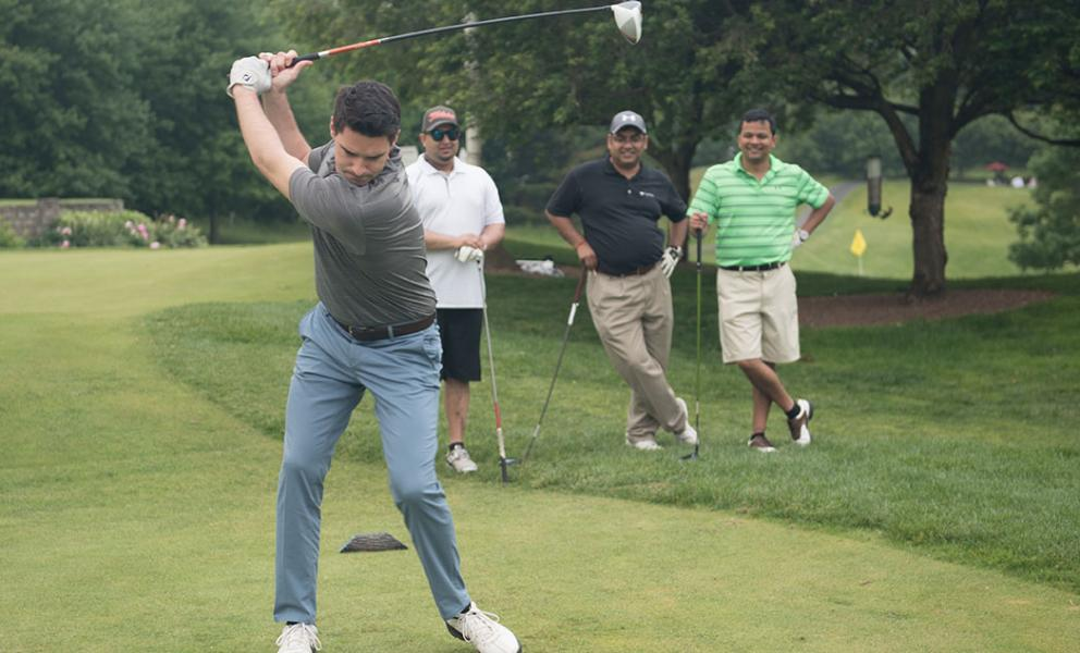 capgemini golfer takes a swing while teammates look on