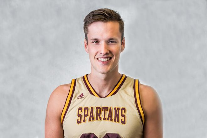 Jules smiling, wearing Spartans Men's Basketball jersey. Gray solid background