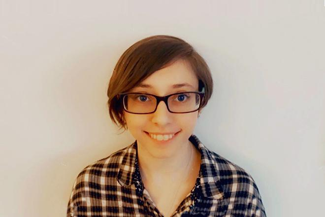Savannah smiling, wearing glasses and flannel shirt