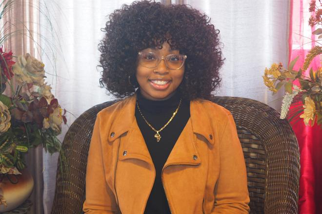 Shaniya smiling, wearing glasses and gold colored blazer, seated.