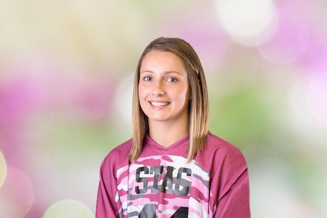 Suzanne Clarke athletics head shot; smiling light green and pink background