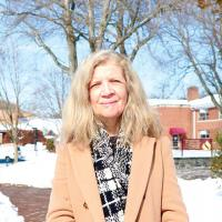 Dr. Finnegan smiling wearing coat and scarf outside with Costello Hall building in background. Snow on the ground.