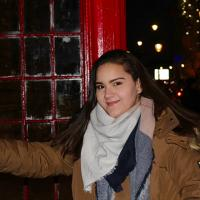 Taylor Trinidad in a red phone booth in London; smiling